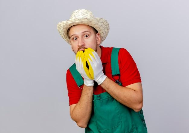 Zaskoczony, młody przystojny ogrodnik słowiański w mundurze na sobie rękawiczki ogrodnicze i kapelusz patrząc, trzymając ręce na ustach na białym tle