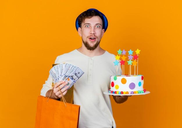 Zaskoczony, młody, przystojny, słowiański, imprezowicz, ubrany w kapelusz imprezowy, trzymając pudełko papierowa torba na pieniądze i tort urodzinowy z gwiazdami, patrząc na kamery na białym tle na pomarańczowym tle