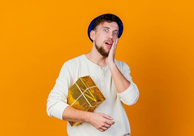Zaskoczony, młody przystojny słowiański imprezowicz w kapeluszu imprezowym, trzymając pudełko, patrząc na aparat, dotykając twarzy na białym tle na pomarańczowym tle z miejsca na kopię
