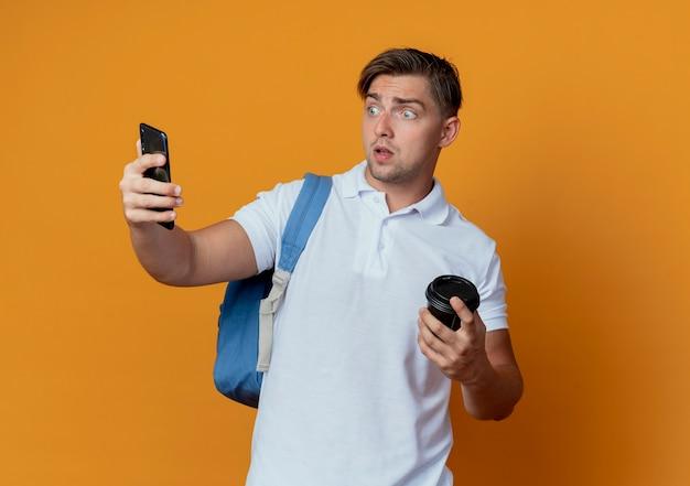 Zaskoczony, młody przystojny student płci męskiej na sobie tylną torbę, trzymając filiżankę kawy
