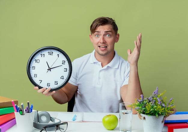 Zaskoczony młody przystojny student płci męskiej siedzi przy biurku z narzędziami szkolnymi, trzymając zegar ścienny i rozłożoną rękę na białym tle na oliwkowej zieleni