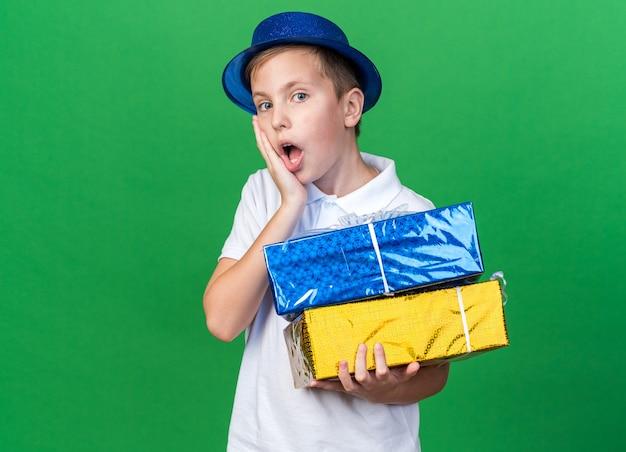 Zaskoczony młody słowiański chłopak w niebieskiej imprezowej czapce, kładący dłoń na twarzy i trzymający pudełka na prezenty na zielonej ścianie z miejscem na kopię
