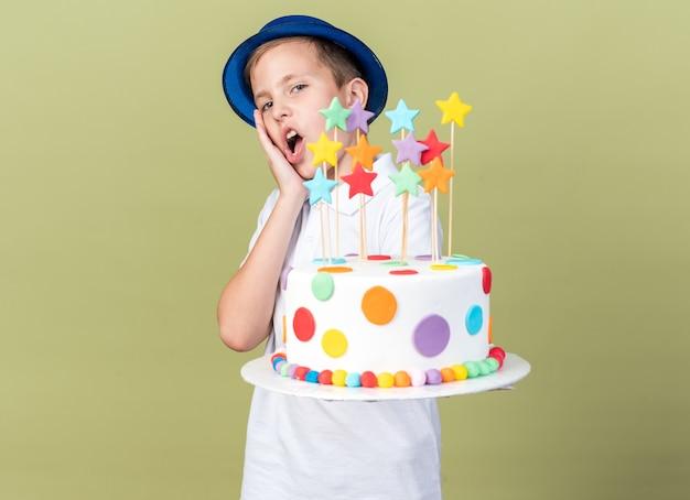 Zaskoczony młody słowiański chłopak w niebieskiej imprezowej czapce, kładący dłoń na twarzy i trzymający tort urodzinowy odizolowany na oliwkowozielonej ścianie z miejscem na kopię