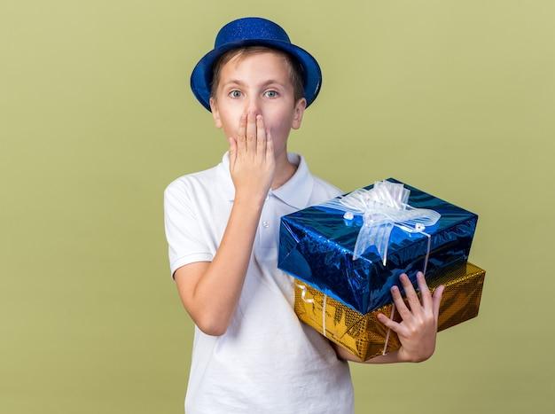 Zaskoczony młody słowiański chłopiec w niebieskiej imprezowej czapce, kładący dłoń na ustach i trzymający pudełka na prezenty na oliwkowo-zielonej ścianie z miejscem na kopię