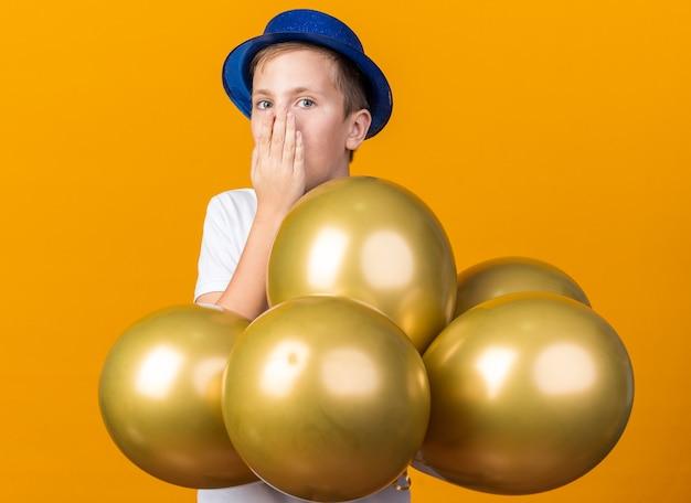 Zaskoczony młody słowiański chłopiec w niebieskiej imprezowej czapce stojący z balonami z helem kładący rękę na ustach odizolowany na pomarańczowej ścianie z kopią przestrzeni