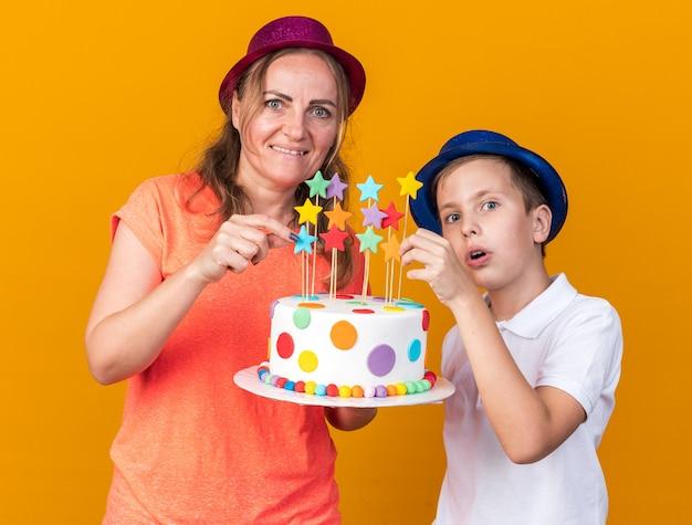 Zaskoczony młody słowiański chłopiec w niebieskim kapeluszu imprezowym trzymający tort urodzinowy z matką w fioletowym kapeluszu imprezowym odizolowanym na pomarańczowej ścianie z miejscem na kopię