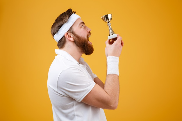 Zaskoczony młody sportowiec posiadający nagrodę