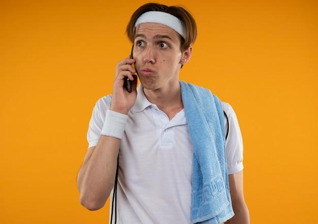Zaskoczony młody sportowy facet patrząc z boku na sobie opaskę na głowę i opaskę z ręcznikiem na ramieniu mówi przez telefon na białym tle na pomarańczowej ścianie
