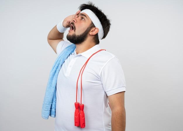 Zaskoczony młody sportowy mężczyzna patrząc w górę z opaską i opaską na rękę z ręcznikiem i skakanką na ramieniu, kładąc dłoń na oku na białej ścianie