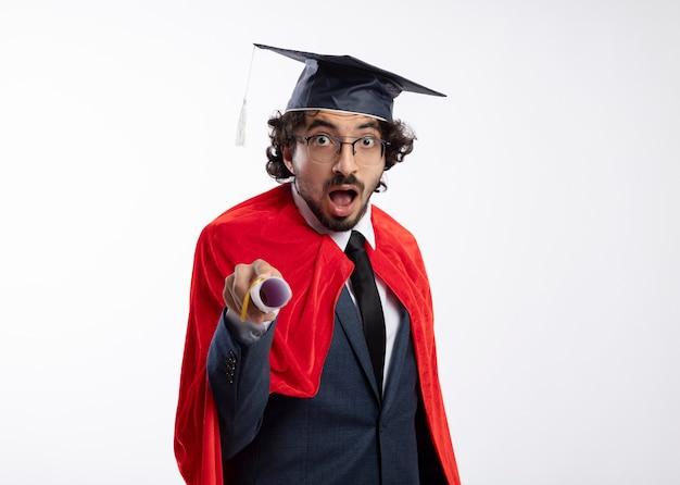 Zaskoczony młody superbohater kaukaski mężczyzna w okularach optycznych, ubrany w garnitur z czerwoną peleryną i czapką ukończenia szkoły, posiada dyplom