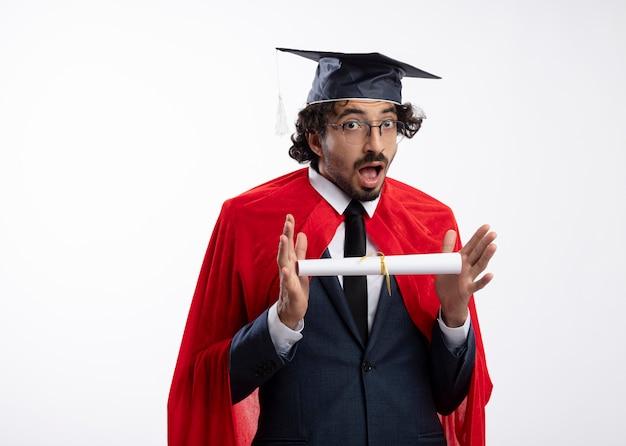 Zaskoczony młody superbohater kaukaski mężczyzna w okularach optycznych, ubrany w garnitur z czerwoną peleryną i czapką ukończenia szkoły, trzyma dyplom i patrzy na kamerę