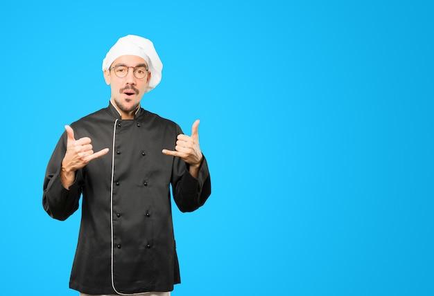 Zaskoczony młody szef kuchni wykonujący gest wołania ręką