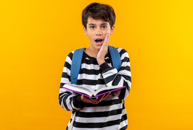 Zaskoczony młody szkolny chłopiec ubrany w plecak, trzymający książkę, kładący rękę na policzku odizolowany na pomarańczowej ścianie