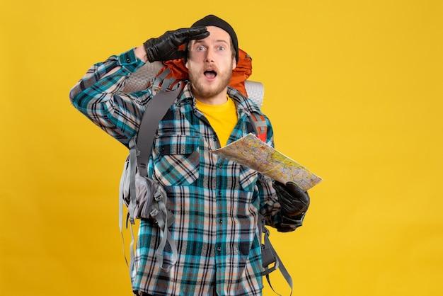 Zaskoczony młody turysta w czarnym kapeluszu trzymający mapę