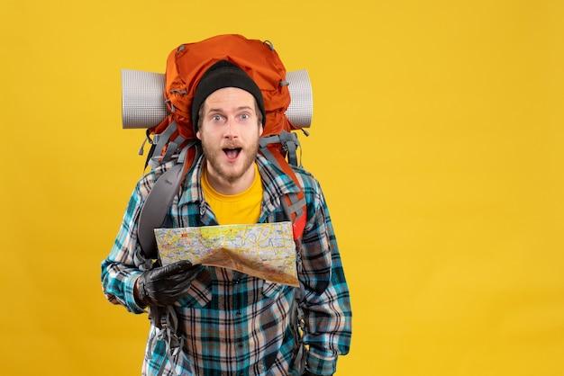 Zaskoczony młody turysta w skórzanych rękawiczkach trzymający mapę