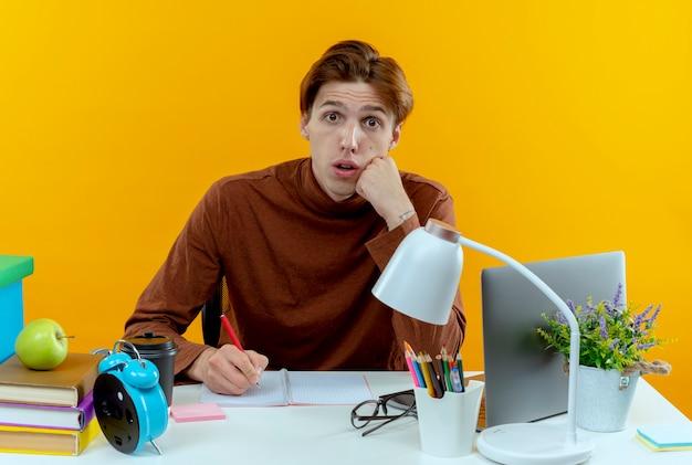 Zaskoczony młody uczeń chłopiec siedzi przy biurku z narzędzi szkolnych, pisząc coś na notebooku na białym tle na żółtej ścianie