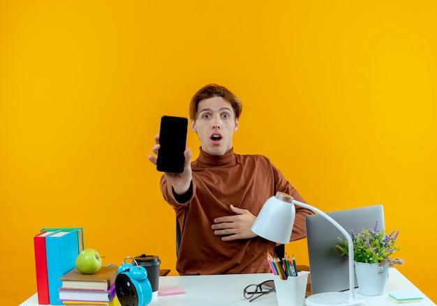 Zaskoczony młody uczeń chłopiec siedzi przy biurku z narzędzi szkolnych, trzymając telefon na białym tle na żółtej ścianie