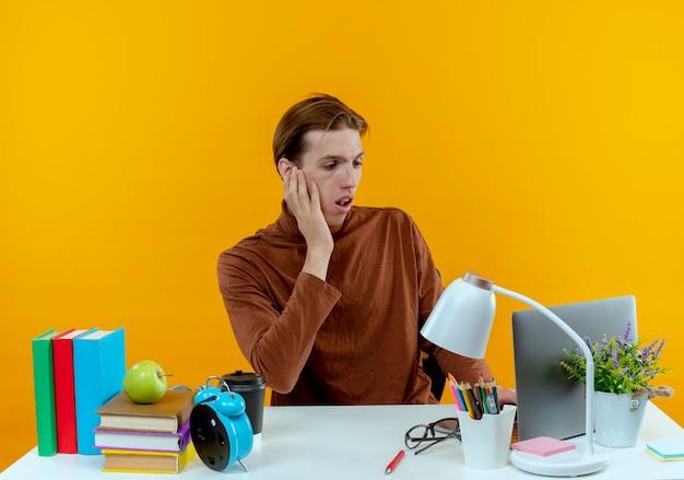 Zaskoczony młody uczeń chłopiec siedzi przy biurku z narzędzi szkolnych używany laptop i kładąc rękę na policzku na żółto