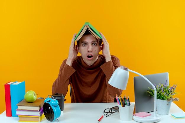 Zaskoczony młody uczeń chłopiec siedzi przy biurku z narzędziami szkolnymi objętych głową z książką na białym tle na żółtej ścianie