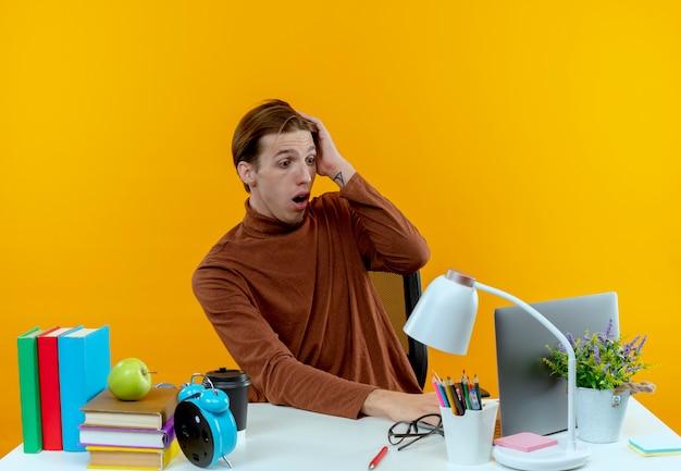 Zaskoczony młody uczeń chłopiec siedzi przy biurku z narzędziami szkolnymi używany laptop i kładąc rękę na głowie na żółto