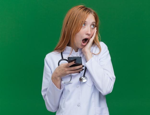 Zaskoczony młody żeński lekarz imbirowy ubrany w szatę medyczną i stetoskop trzymający telefon komórkowy patrzący na bok trzymając rękę na twarzy odizolowanej na zielonej ścianie z kopią przestrzeni