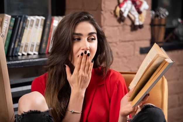 Zaskoczony model kobieta siedzi i czyta książkę.