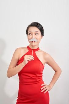 Zaskoczony model mrugając dziewczyna trzyma śmieszne wąsy na patyku na białym tle.