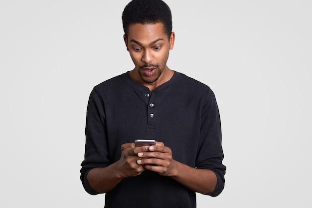 Zaskoczony murzyn trzyma nowoczesną komórkę, otrzymuje nieoczekiwaną wiadomość tekstową, surfuje po stronie internetowej, ubrany w zwykłe ubrania, czuje się zszokowany