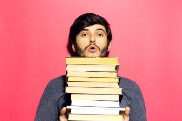Zaskoczony nastolatek w okrągłych okularach z bukietem książek w ręce na ścianie różowego koralowca.
