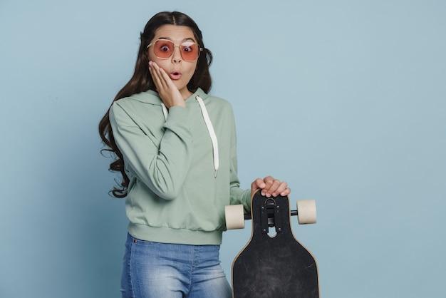 Zaskoczony nastolatka trzyma deskorolkę w okularach przeciwsłonecznych. dziewczyna na deskorolce dotyka swoich policzków na niebieskim tle
