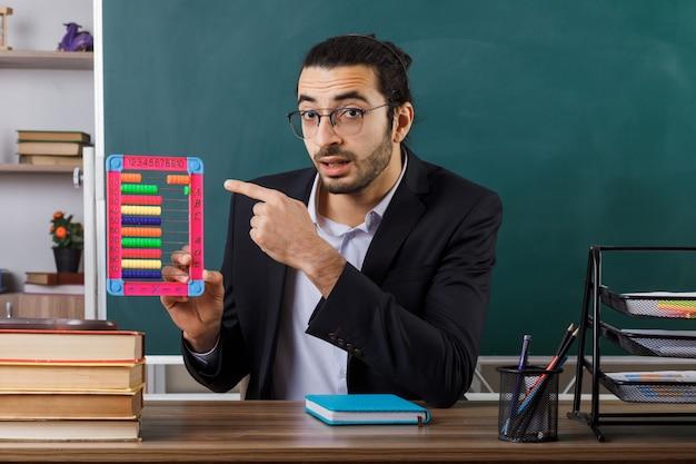 Zaskoczony nauczyciel w okularach, trzymający i wskazujący na liczydło, siedzący przy stole z szkolnymi narzędziami w klasie