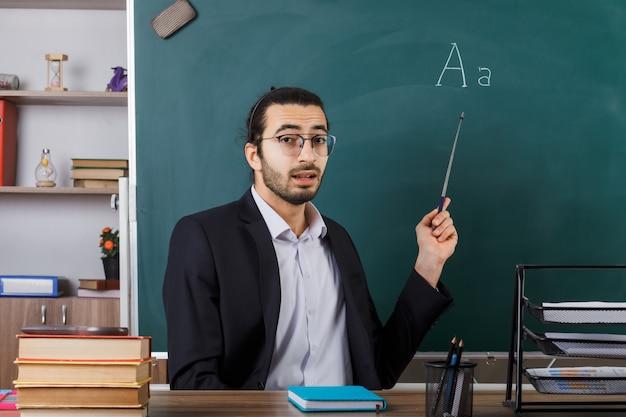 Zaskoczony nauczyciel w okularach wskazuje na tablicę kijem wskaźnikowym siedzącym przy stole z narzędziami szkolnymi w klasie