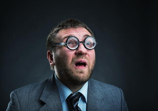 Zaskoczony nerd biznesmen w okularach na szarym