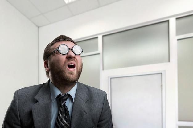 Zaskoczony nerd biznesmen w okularach w biurze