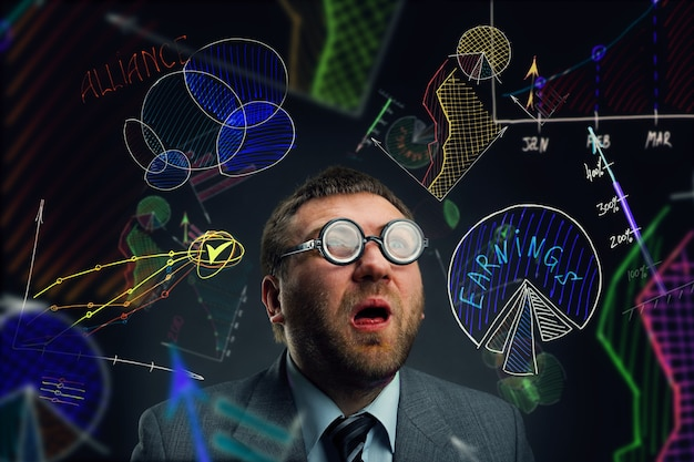 Zaskoczony nerd biznesmen wśród wykresów biznesowych