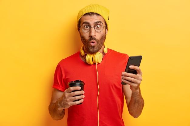 Zaskoczony nieogolony facet słucha muzyki w słuchawkach, wysyła sms-y na komórkę, typuje odpowiedź