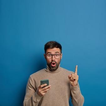 Zaskoczony, nieogolony mężczyzna trzyma telefon, pokazuje pustą przestrzeń powyżej, wskazuje palcem wskazującym, nosi okulary i brązowy sweter, trzyma usta otwarte, odizolowany na niebieskim tle.