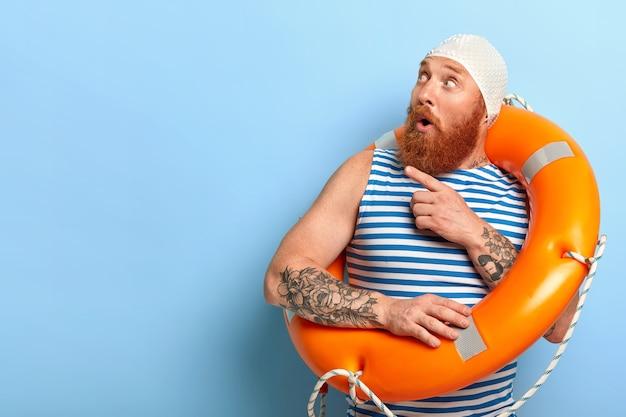Zaskoczony nieogolony urlopowicz ubrany w czepek kąpielowy i kamizelkę w paski