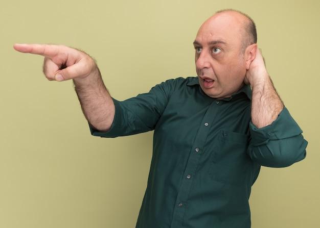 Zaskoczony, patrząc na boczny mężczyzna w średnim wieku, ubrany w zieloną koszulkę, kładący dłoń za punktami głowy z boku odizolowany na oliwkowej ścianie