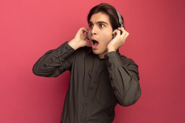 Zaskoczony, patrząc na bok młody przystojny facet ubrany w czarną koszulkę ze słuchawkami na białym tle na różowej ścianie