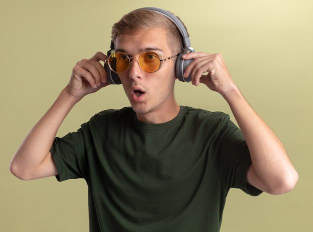 Zaskoczony, patrząc na bok młody przystojny facet ubrany w zieloną koszulę z okularami i słuchawkami na białym tle na oliwkowej ścianie