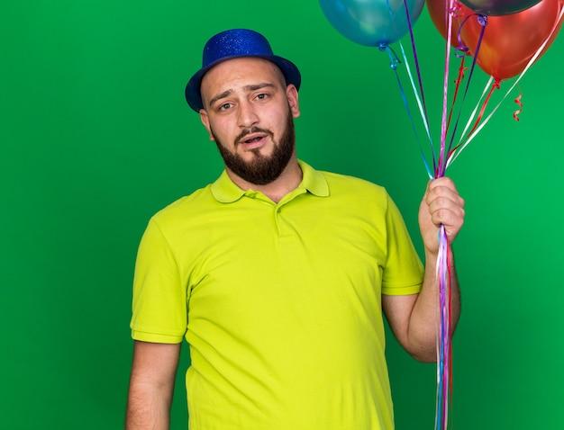Zaskoczony, patrząc na kamerę, młody człowiek ubrany w niebieski kapelusz imprezowy trzymający balony