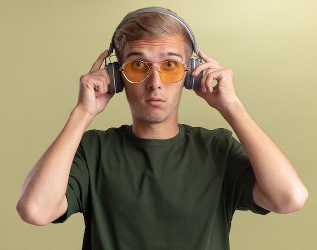Zaskoczony, patrząc na przód młody przystojny facet ubrany w zieloną koszulę w okularach i słuchawkach na białym tle na oliwkowej ścianie
