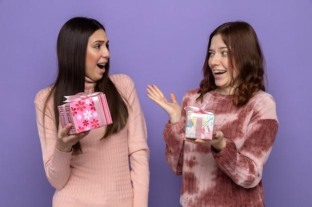 Zaskoczony patrząc na siebie dwie dziewczyny w szczęśliwy dzień kobiety trzymające prezenty izolowane na niebieskiej ścianie