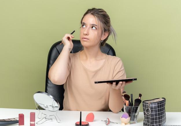 Zaskoczony patrząc z boku młoda piękna dziewczyna siedzi przy stole z narzędziami do makijażu, trzymając pędzel z paletą cieni do powiek na oliwkowym tle