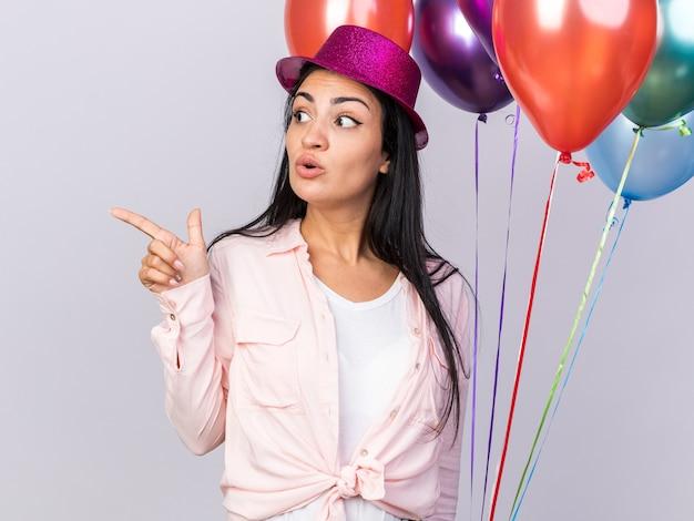 Zaskoczony patrząc z boku młoda piękna dziewczyna w kapeluszu imprezowym, trzymająca balony i punkty z boku na białym tle na białej ścianie z miejscem na kopię