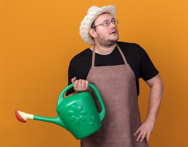 Zaskoczony, patrząc z boku młody mężczyzna ogrodnik w kapeluszu ogrodniczym trzymając konewkę, kładąc rękę na biodrze na białym tle na pomarańczowej ścianie