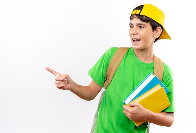 Zaskoczony, patrzący na bok młody szkolny chłopiec ubrany w plecak z czapką wskazuje z boku na białym tle na białej ścianie z miejscem na kopię