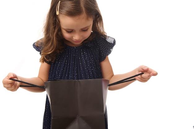 Zaskoczony piękna 4 lata dziewczynka mała dziewczynka ubrana w wieczorową ciemnoniebieską sukienkę patrząc na czarny pakiet zakupów, na białym tle z miejsca kopiowania. koncepcja czarnego piątku