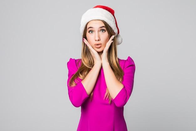 Zaskoczony piękna dziewczyna ze złotymi włosami w różowej sukience i noworocznym kapeluszu na białym tle